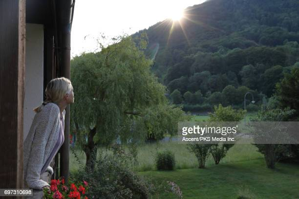 Woman leans from railing to view sunrise, mountains