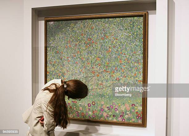 A woman leans in for a closeup look at Gustav Klimt's 'Apple Tree I' at Christie's auction house Tuesday November 7 in New York The Klimt oil on...