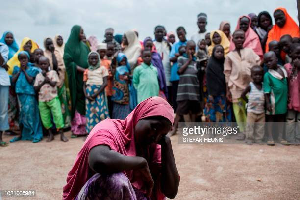 TOPSHOT A woman leans on her hand while others look on outside a tent in one of the IDP camps in Pulka on August 1 2018 As the presidential race...