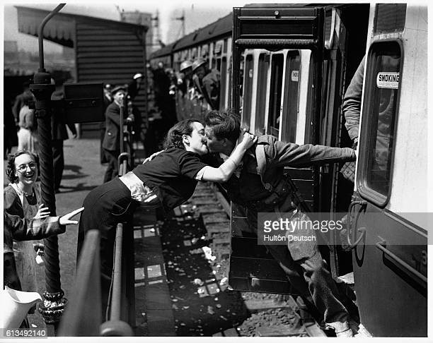Woman leans over the railings at a railway station to kiss a soldier of the British Expeditionary Forces returning from the front of the Second World...