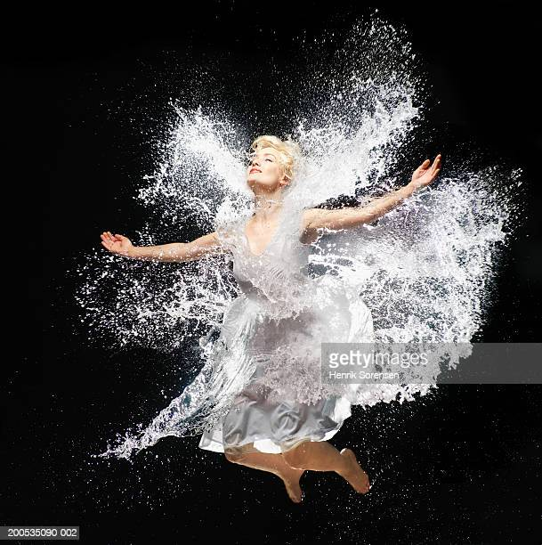 Woman leaping against black background splashed with water