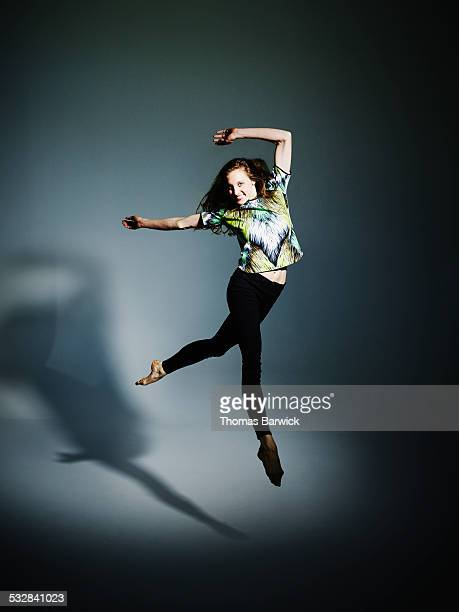 Woman leaping in mid air with arms overhead