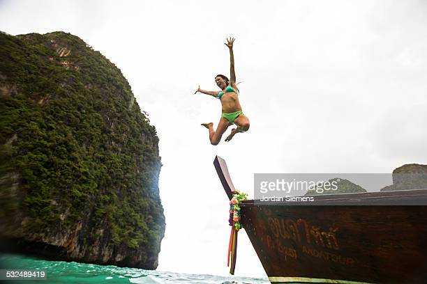 A woman leaping into tropical water.