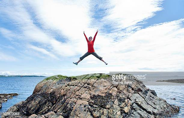 Woman leaping on a rock
