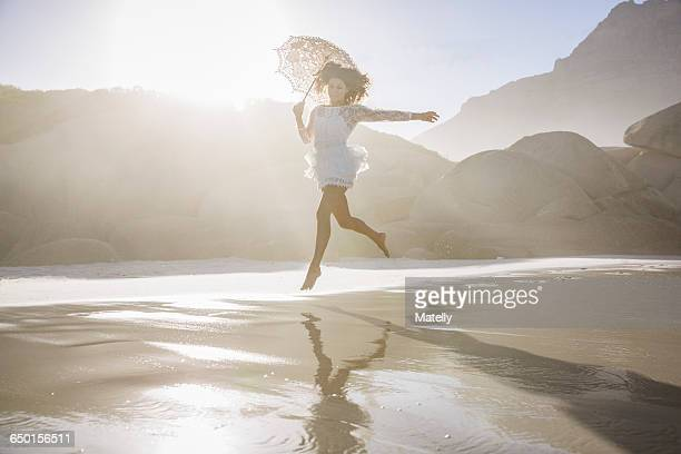 Woman leaping on beach wearing short white dress holding umbrella