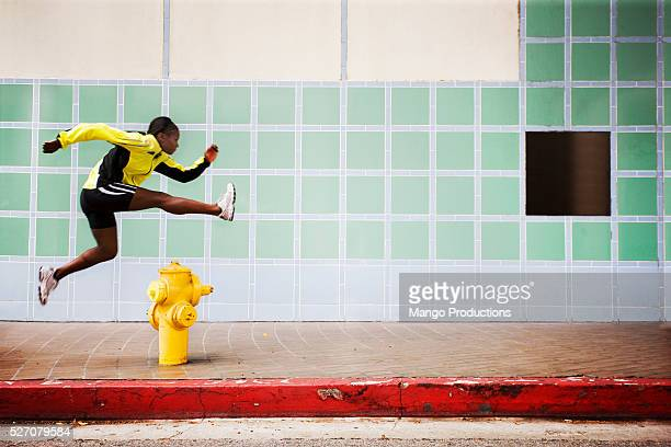Woman leaping over a fire hydrant
