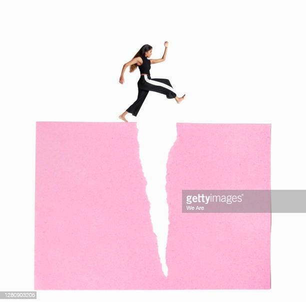 woman leaping over crack - young women stock pictures, royalty-free photos & images