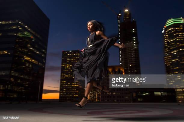 Femme sautant sur l'hélisurface sur le toit du gratte-ciel