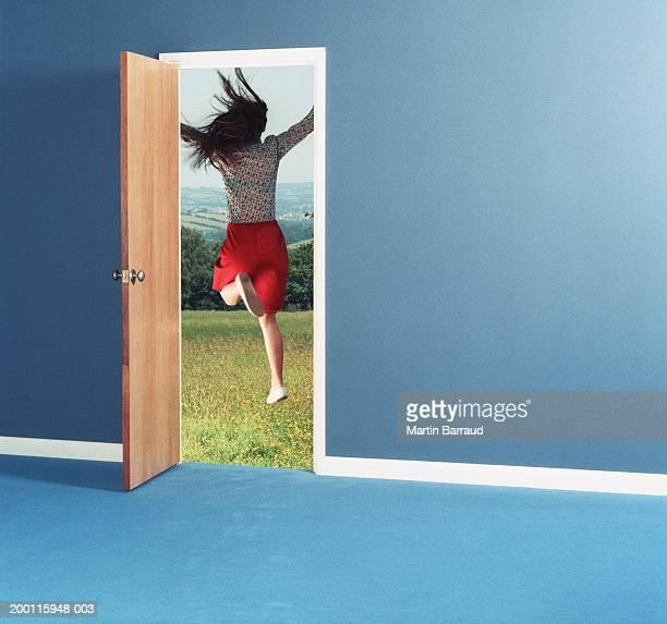 woman leaping through doorway into field, rear view - partida fotografías e imágenes de stock