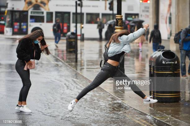 Woman leaps over a puddle on Oxford Street following heavy rain on October 02, 2020 in London, England.