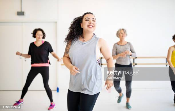 woman learning dance moves in a class - large group of people photos et images de collection