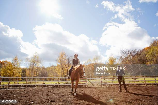 Woman learning how to ride on horse in pasture