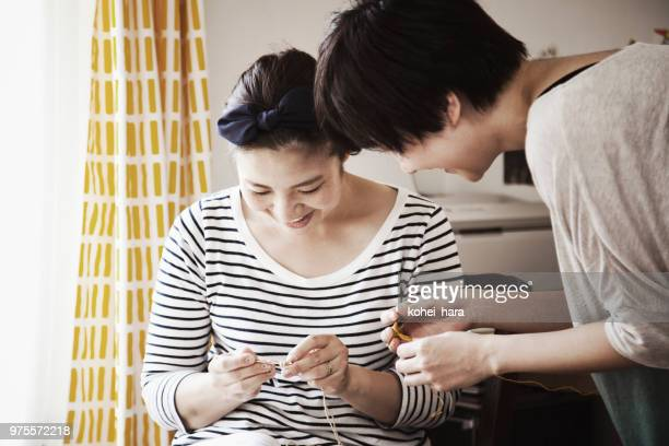 Woman learning sewing from female instructor