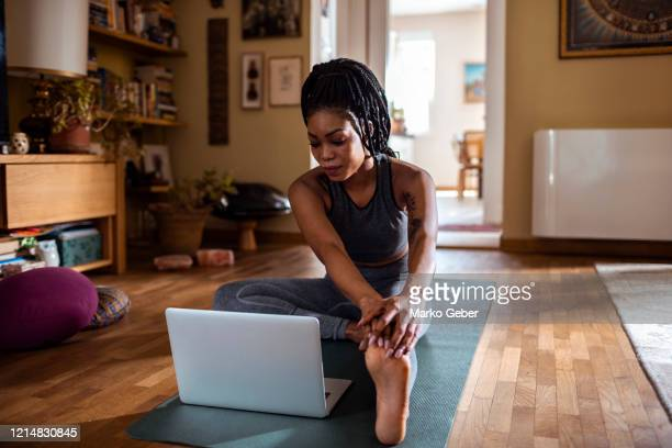 woman learning the janu sirsasana pose - welzijn stockfoto's en -beelden