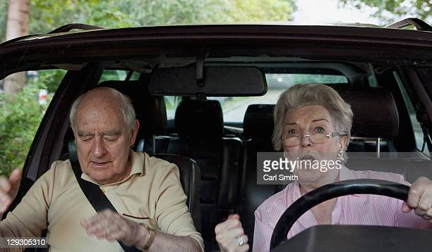 Woman learning to drive gets excited while man in passenger seat appeals for calm