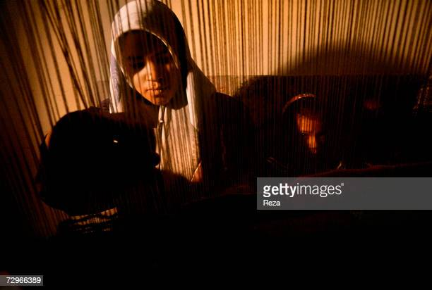 A woman learns to make carpets in a weaving workshop on April 2000 in Tripoli Libya
