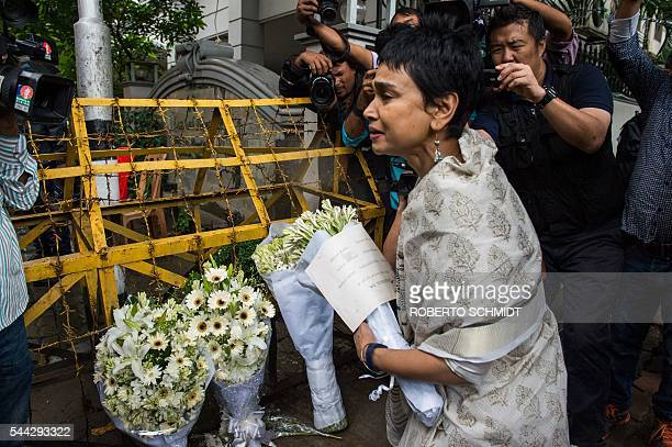 A woman leaves a floral arrangement on a road block leading to an upscale cafe in Dhaka on July 3 2016 that was the site of a bloody siege Bangladesh...