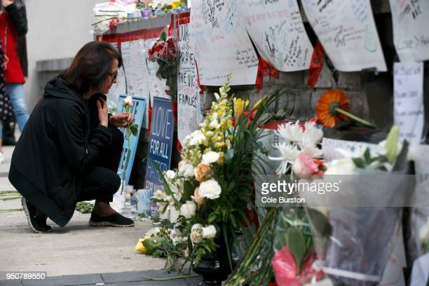 A woman leaves a flower at a memorial for victims of the mass killing on Yonge St at Finch Ave on April 24 2018 in Toronto Canada A suspect...