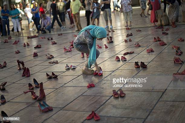 A woman leaves a note in a pair of red shoes at the Constitucion square in Malaga where the Mexican artist Elina Chauvet's artinstallation 'Zapatos...