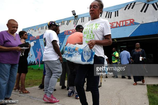 A woman leaves a recreation center after receiving free bottled water on August 13 2019 in Newark New Jersey Residents of Newark the largest city in...