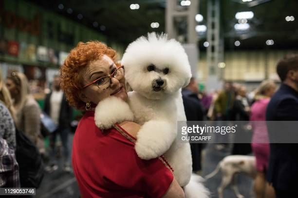 A woman leaves a show ring with her bichon frise dog after taking part in the Eukanuba World Challenge competition on the first day of the Crufts dog...