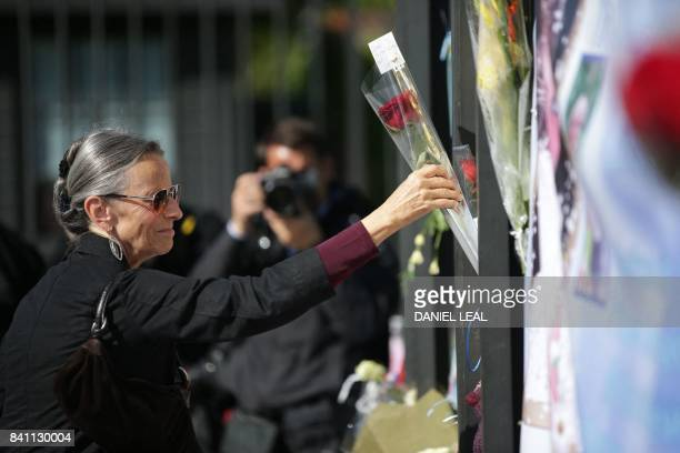 A woman leaves a single red rose among the tributes of flowers candles and photographs outside one of the gates of Kensington Palace in London on...