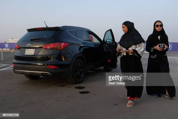 A woman leaves a station where she sat in a car while an instructor demonstrated a parking technique during an outdoor educational driving event for...