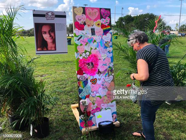 Woman leaves a tribute in front of the memorial of one of the 17 victims of Marjory Stoneman Douglas High School shooting in Parkland, Florida during...