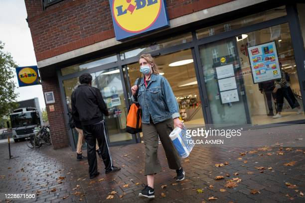 Woman leaves after puchasing toilet paper at Lidl supermarket in Walthamstow, east London on September 23, 2020. - Britain on Tuesday tightened...