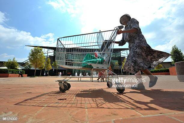 A woman leaves after shopping at Maponya Mall in Soweto on March 19 2010 This is the new Soweto a mix of uppercrust comforts and urban grit where...