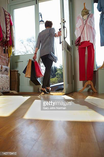 woman leaves boutique shop with bags - leaving stock pictures, royalty-free photos & images