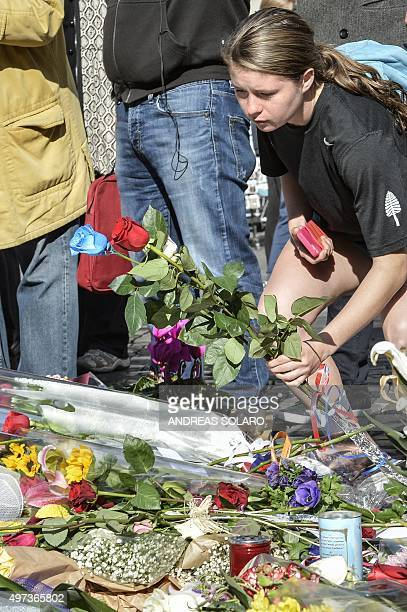 A woman leaves flowers as she takes a moment to pay her respects ahead of a minute of silence on November 16 2015 in front of the French embassy at...