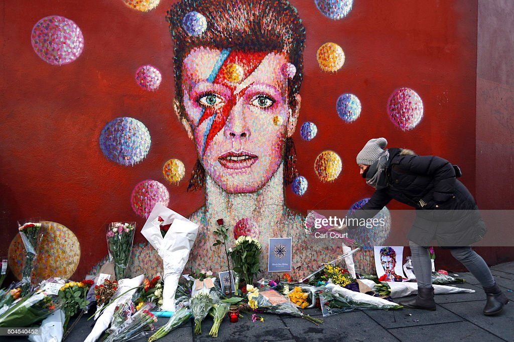A woman leaves flowers beneath a mural of David Bowie in Brixton on January 11, 2016 in London, England. British music and fashion icon David Bowie died earlier today at the age of 69 after a battle with cancer.