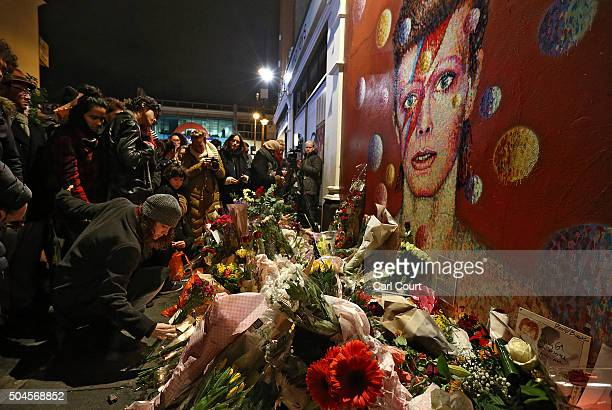 A woman leaves flowers beneath a mural of David Bowie in Brixton on January 11 2016 in London England British music and fashion icon David Bowie died...