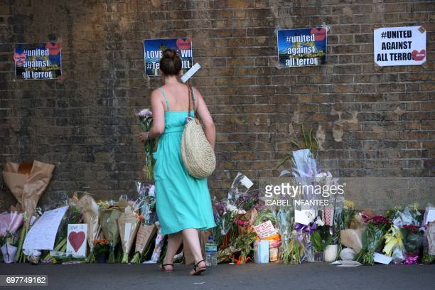 A woman leaves flowers close to the scene of a van attack in Finsbury Park north London on June 19 2017 Ten people were injured when a van drove into...