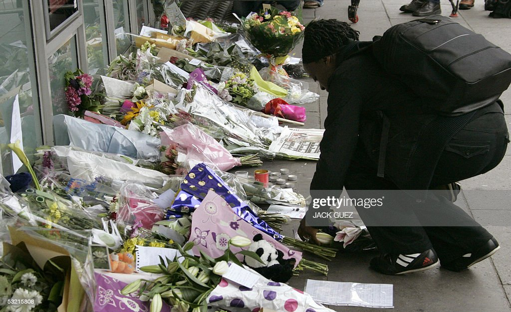 A woman leaves flowers in memory of the victimes of the bomb blasts at King's Cross in London 09 July 2005. Police investigating the London bomb blasts were probing extremist groups linked to Al-Qaeda as recovery teams tried to pull yet more bodies from a wrecked subway train, fearing the final death toll could climb well above the current 50.