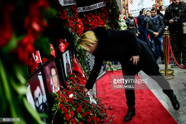 A woman leaves flowers next to portraits of victims in front of the Reina nightclub in Istanbul on December 31 a year after an attack on the club...