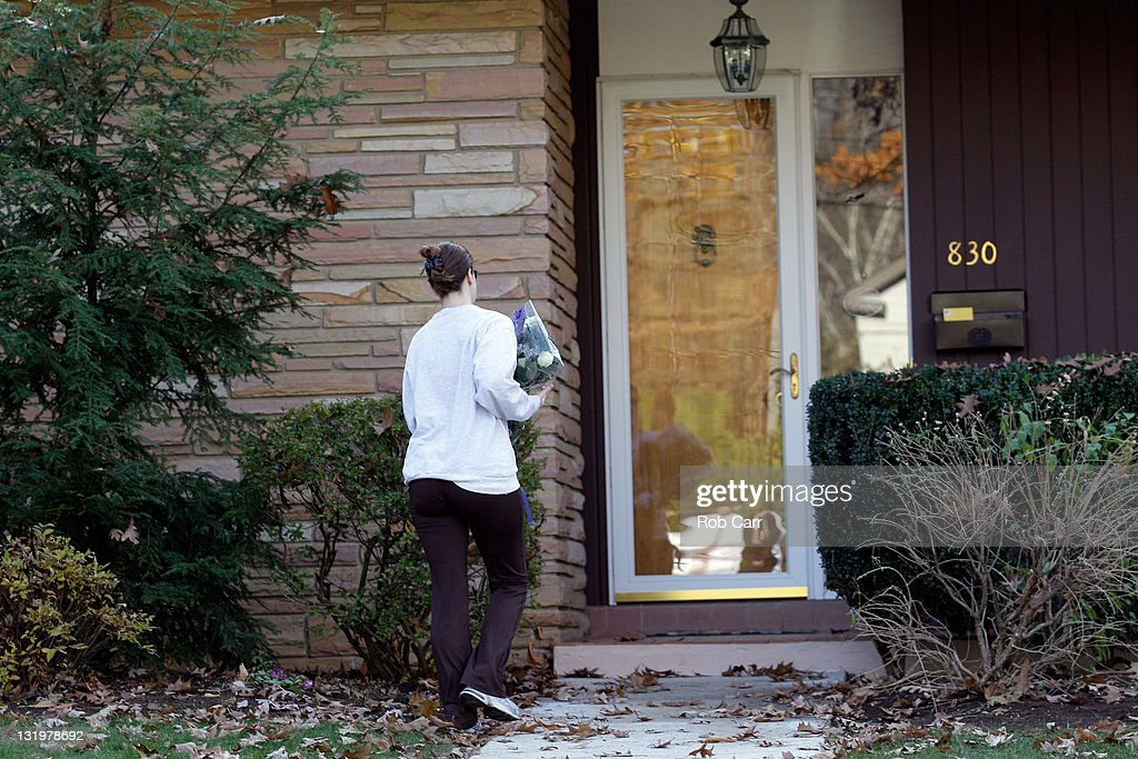 A woman leaves flowers on the front steps of Penn State University head football coach Joe Paterno's home on November 9, 2011 in State College, Pennsylvania.