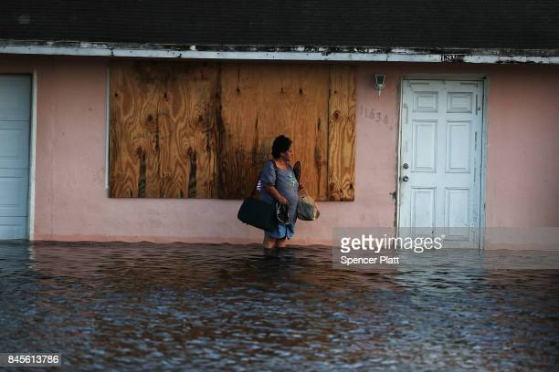 A woman leaves her flooded home the morning after Hurricane Irma swept through the area on September 11 2017 in Fort Myers Florida Hurricane Irma...