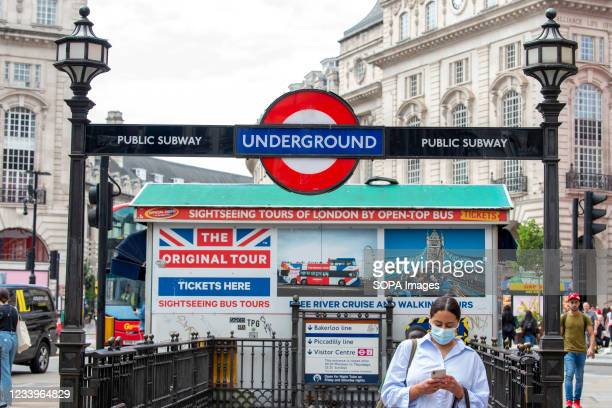 Woman leaves Piccadilly Circus underground station wearing a face mask. The mandatory wearing of Face masks on public transport in England is to end...