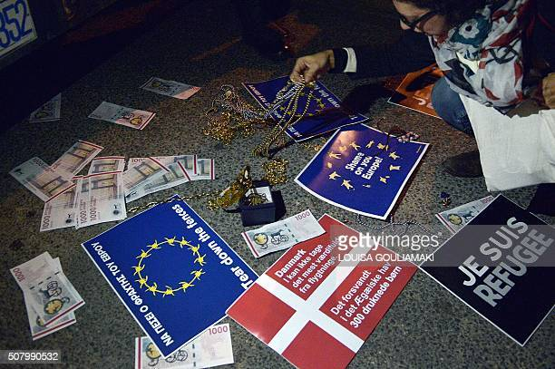 A woman leaves some jewelry in front of police officers standing guard in front of the Danish embassy in Athens during a protest by promigrant...