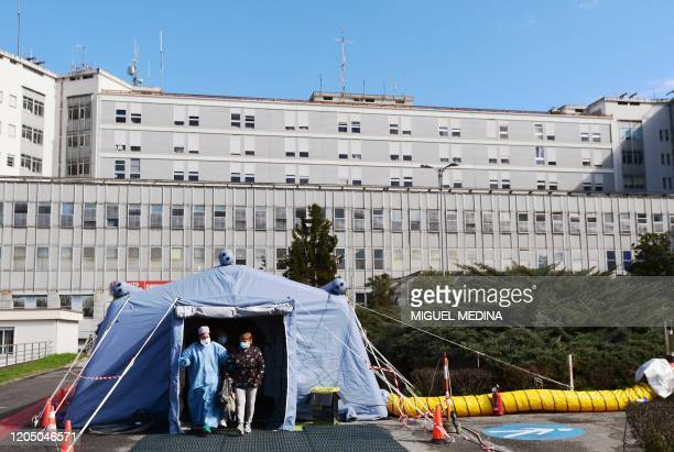 TOPSHOT A woman leaves the a pretriage medical tent in front of the Cremona hospital in Cremona northern Italy on March 4 2020 Italy will recommend...