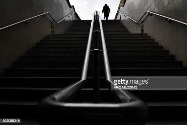 TOPSHOT A woman leaves the closed entrance of an Athens' metro station during a 24hours general strike on January 15 2018 New Greek strikes to...
