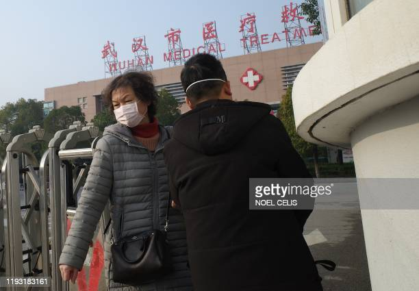 A woman leaves the Wuhan Medical Treatment Centre where a man who died from a respiratory illness was confined in the city of Wuhan Hubei province on...