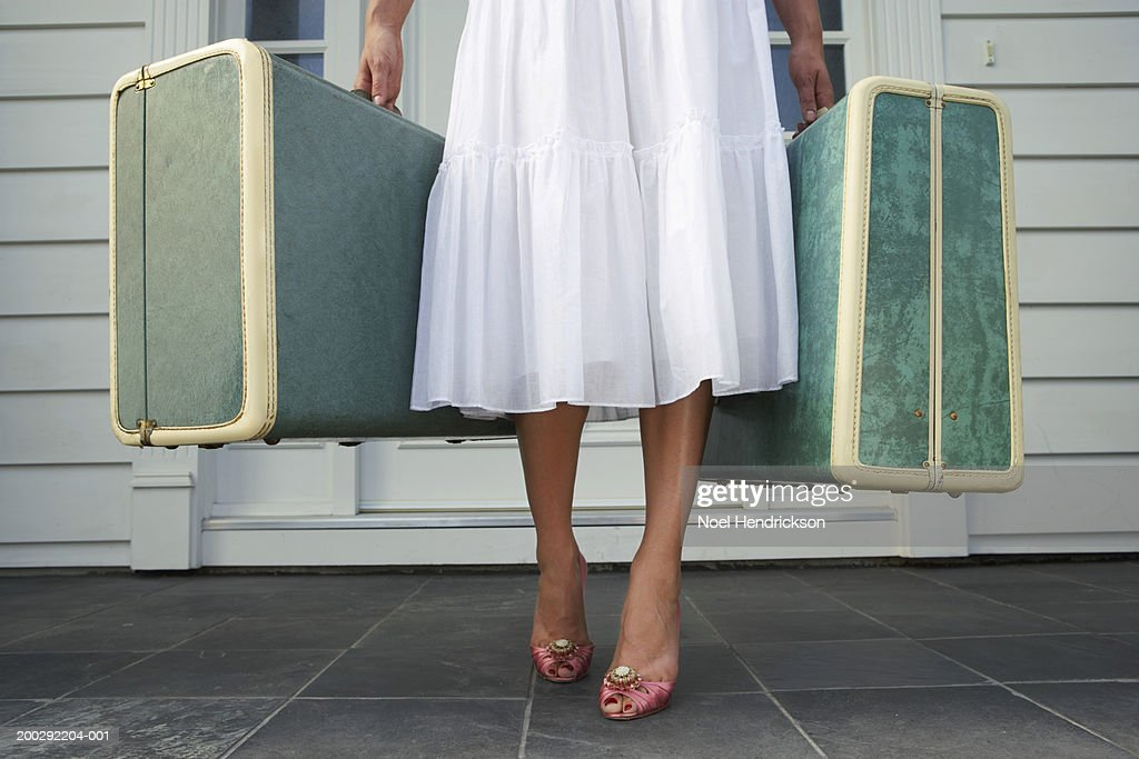 Woman leaving entrance door carrying two suitcases, low section : Stock Photo