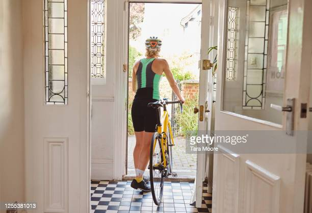 woman leaving house on bicycle - summer stock pictures, royalty-free photos & images