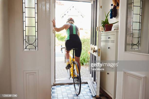 woman leaving house on bicycle - headwear stock pictures, royalty-free photos & images