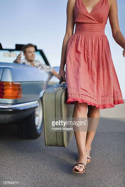 Woman leaving man in convertible