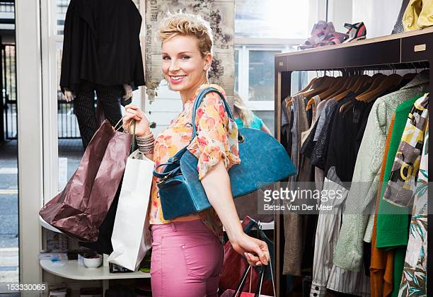 Woman leaving shop with shopping bags.