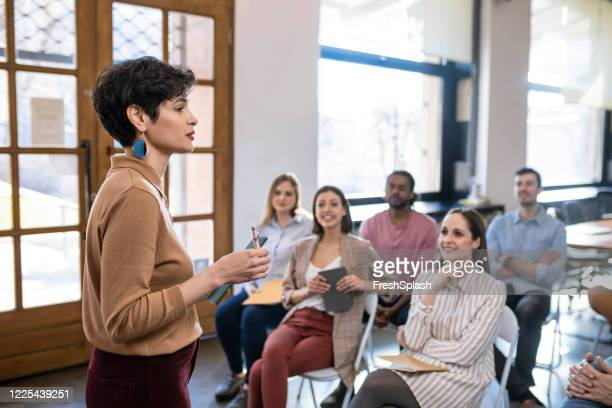 woman lecturer giving presentation to businesspeople at a modern company - candidate stock pictures, royalty-free photos & images